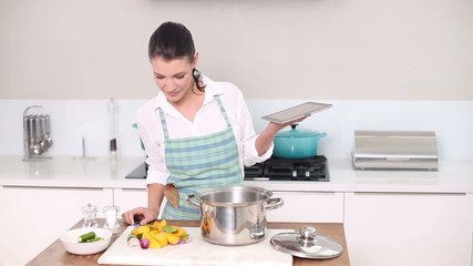 Beautiful brunette following a recipe while making dinner