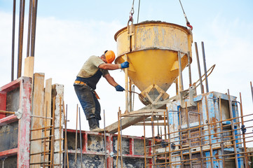 building workers pouring concrete with barrel