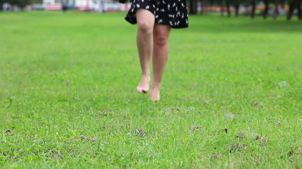 Woman without her shoes and running on green grass field