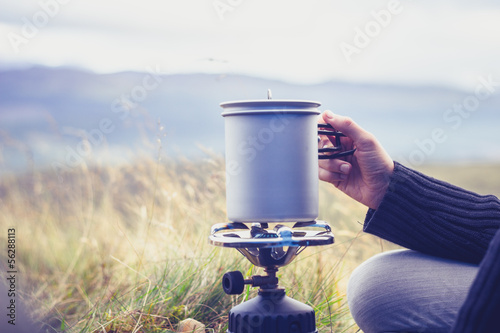 Foto op Canvas Kamperen Woman boiling water on portable camping stove