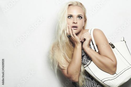 beautiful blond woman with white handbag.she surprised