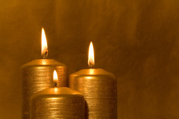 Three golden candles burning in the grunge background