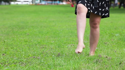 Woman in dress throwing off her shoes and walking on green grass