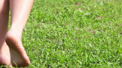 Close-up view of female legs walking tiptoe on green field