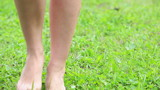 Female legs walking on green grass in summer field