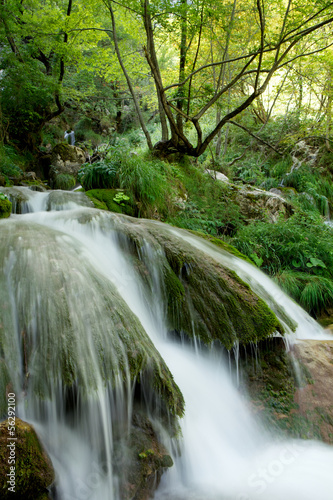 Waterfall between rocks in green environment