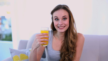 Happy model drinking orange juice on the couch