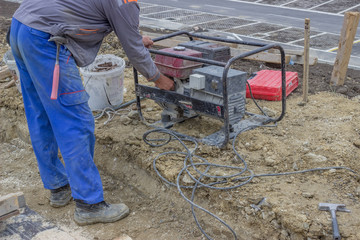 Construction Worker starts the portable Electric Generator 2