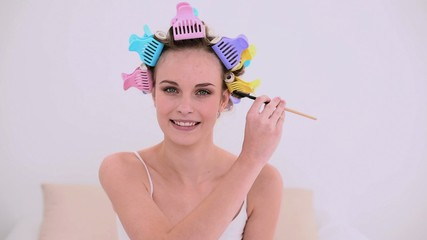 Young model in hair rollers brushing her eyebrows