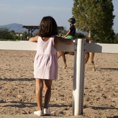Niña viendo a otro niño montar en caballo