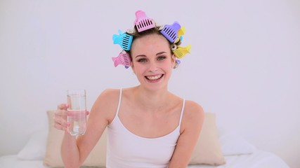 Young model in hair rollers drinking glass of water