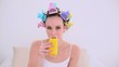 Young model in hair rollers drinking glass of orange juice