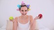Young model in hair rollers holding red and green apples