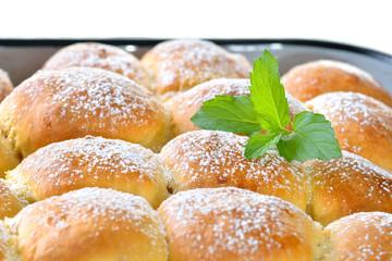 Frisch gebackene Buchteln mit Puderzucker und Minzeblatt