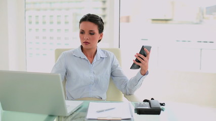 Worried businesswoman making calculations