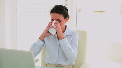 Businesswoman drinking coffee and feeling revitalized