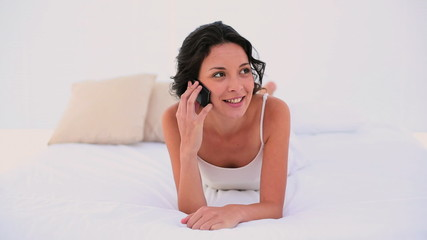 Brunette lying on bed and chatting on the phone