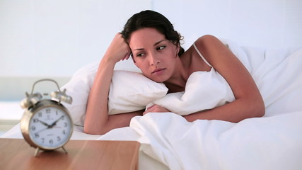 Brunette lying in bed feeling tired in the morning