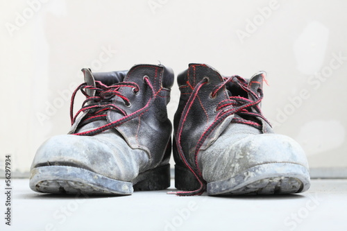 pair of old dirty work boots in building site - 56297934