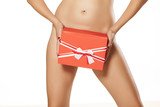 naked woman posing with gift over pubic area