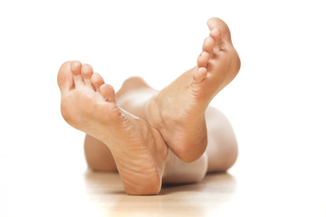 naked woman lying on the floor with a focus on feet