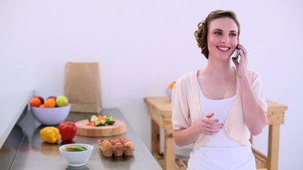 Pretty model standing in kitchen talking on the phone