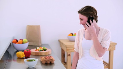 Pretty model standing in kitchen chatting on the phone