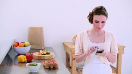 Pretty model standing in kitchen texting on her phone