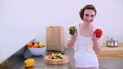 Pretty model taking peppers from grocery bag