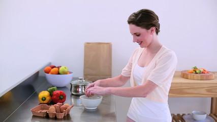 Pretty model standing in kitchen preparing an omelette