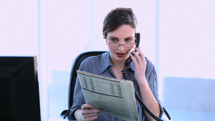 Pretty businesswoman answering phone and reading newspaper