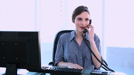 Pretty businesswoman answering phone