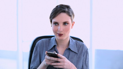 Happy businesswoman texting on her smartphone