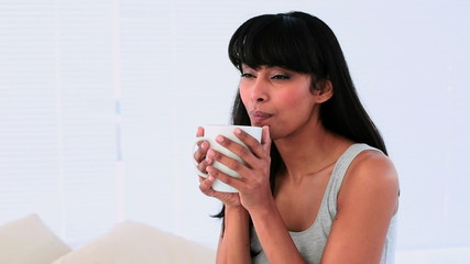 Attractive woman enjoying her morning coffee on her bed