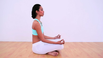Peaceful woman meditating in lotus position