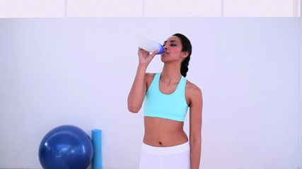Fit woman walking and drinking from sports bottle