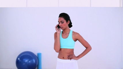 Fit woman chatting on her smartphone and smiling at camera