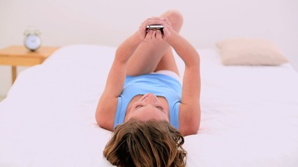 Relaxing brunette lying on her bed using her mobile phone
