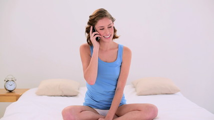 Cheerful brunette sitting on her bed making a phone call