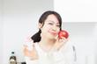リンゴとケーキを持った女性