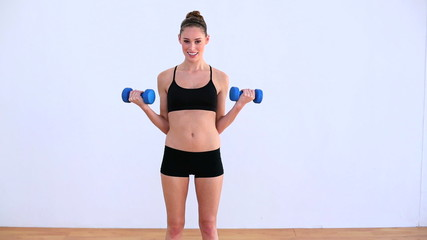 Pleased woman exercising with dumbbells