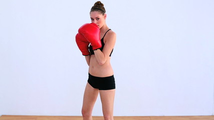 Dynamic woman boxing with red gloves