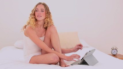 Cheerful blonde model typing on a tablet pc