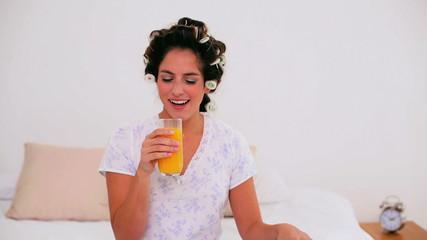 Joyful woman in hair curlers enjoying orange juice