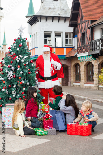 Children With Gifts Looking At Santa Claus