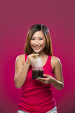 Asian woman holding a drink in a bag on colorful background