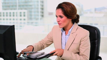 Concentrated attractive businesswoman filling her diary