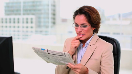 Concentrated attractive businesswoman reading a newspaper