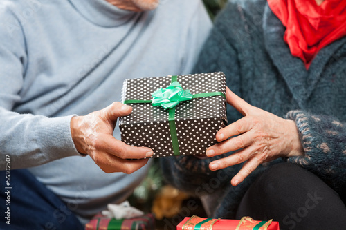 Couple Holding Christmas Present At Store