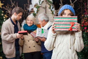 Thoughtful Woman Holding Christmas Present With Family In Backgr